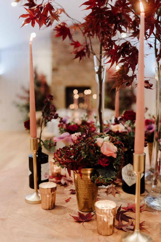 stunning table centre in warm tones of plum red and pops of corals
