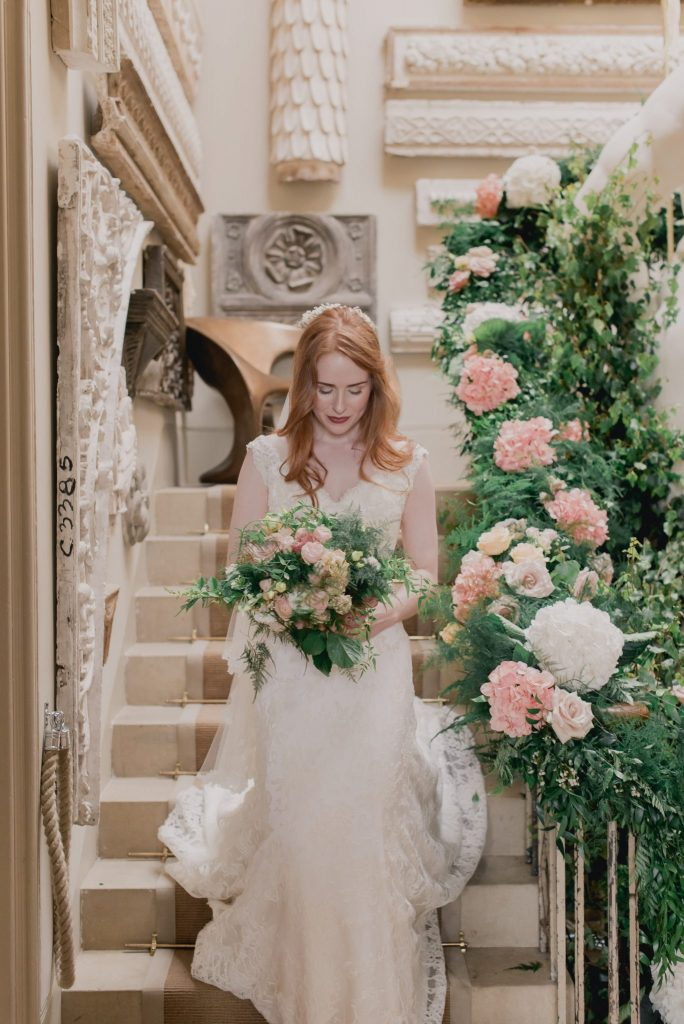 the bride descends the floral staircase at Aynhoe Park with her soft romantic bouquet