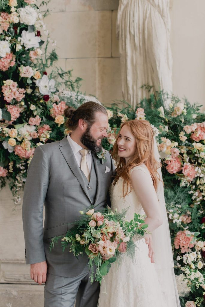Rose and David in front of a floral cascade of dreamy nude toned flowers at Aynhoe Park
